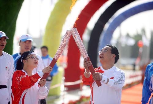 火炬手刘盛春(右)与蒙古族火炬手孟咏梅在进行交接。当日,北京奥运会圣火在青海省格尔木传递。 新华社记者邢广利摄