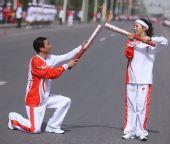 图文:奥运圣火在格尔木传递 彭文情交接