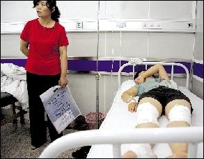 昨天,双腿被打伤的郝女士躺在病床上。本报实习生 李寅 摄