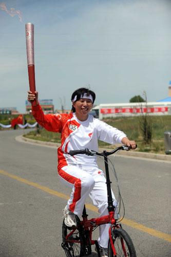火炬手杨艳丽骑着自行车进行传递