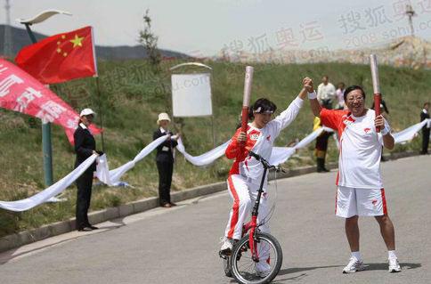 6月23日,火炬青海湖传递,火炬手骑车传递火炬