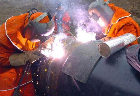 油管道局的施工人员对中哈管道实施最后一道焊口的对接处理。资料图