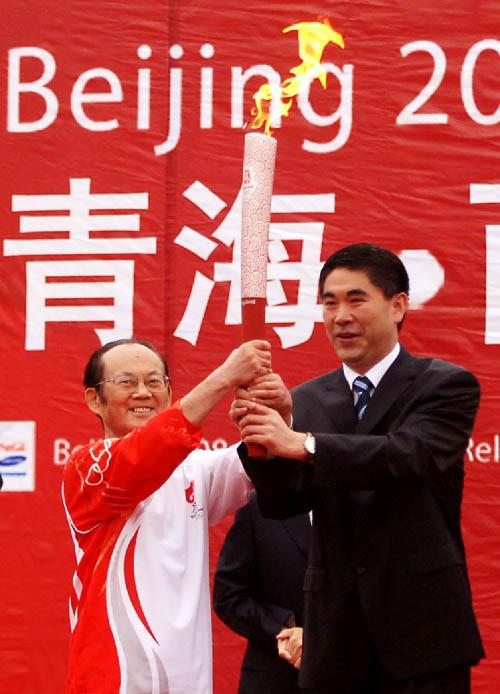第一棒火炬手、中国工程院院士吴天一(塔吉克族)从西宁市委书记王建军(右)手中接过火炬