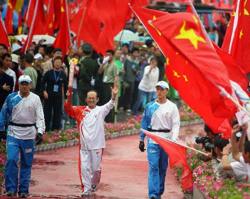 第一棒火炬手、中国工程院院士吴天一(塔吉克族)在进行传递