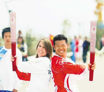 六月二十三日,北京奥运会圣火在青海湖传递。图为火炬手、美国人克纳(左)与上一棒火炬手、美国人保罗交接后合影。
