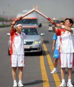 图文:奥运圣火运城传递 贾秋君和郭立在交接