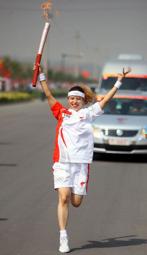 奥运火炬手贾秋君(左)和上一棒火炬手交接。新华社记者邢广利摄