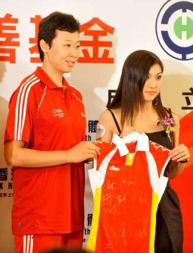 中国女排队长冯坤(左)将签名球衣交予香港体检执行董事蔡加怡