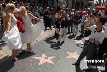 """当地时间6月23日,来自中国广东的赴美旅游首发团成员在好莱坞星光大道与街头艺人""""玛丽莲·梦露""""合影留念。当天,中国赴美旅游团240多位成员汇聚洛杉矶好莱坞,洛杉矶当地旅游部门举行盛大欢迎仪式,欢迎美国成为中国旅游目的地后的首批中国游客。中新社发张炜 摄"""