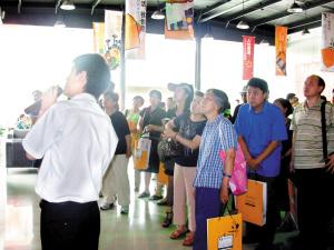 晨报看房团听东亚三环中心销售人员现场介绍楼盘情况。