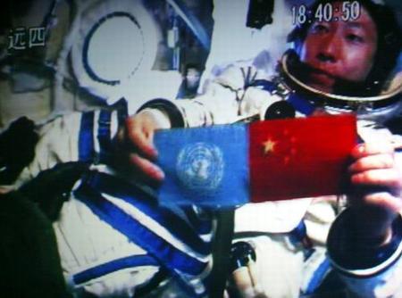 """中国航天员杨利伟乘坐""""神舟五号""""飞船在太空中展示中国国旗和联合国旗。"""