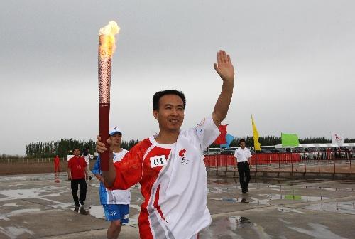 火炬手费俊龙手持火炬传递。当日,北京奥运圣火在东风航天城传递。 新华社记者李刚摄