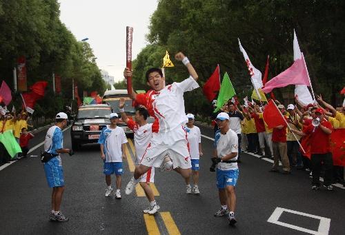 火炬手巩运青手持火炬高高跃起。当日,北京奥运圣火在东风航天城传递。 新华社记者李刚摄