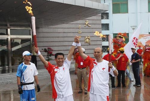 6月28日,火炬手陈炳忠(右)与下一棒火炬手聂海胜交接。当日,北京奥运圣火在东风航天城传递