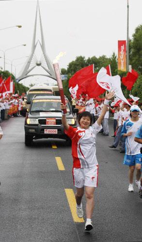 6月28日,火炬手刘慧手持火炬传递。当日,北京奥运圣火在东风航天城传递。 新华社记者李刚摄