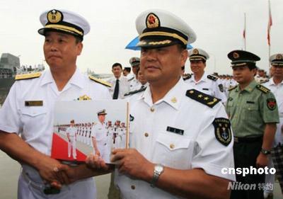 送仪式上,中国人民解放军南海舰队司令苏士亮中将,向担任这次访华舰艇指挥官的日本海上自卫队第四护卫队群司令德丸伸一少将,赠送他们在华活动图片册。中新社发 牛志军 摄