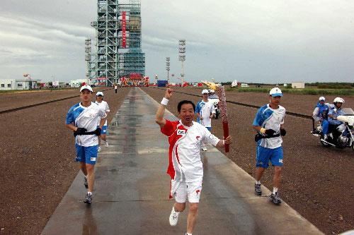 6月28日,火炬手刘明山手持火炬传递。当日,北京奥运圣火在东风航天城传递。 新华社记者李刚摄