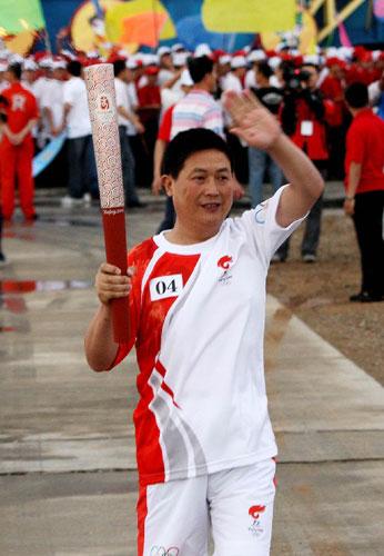 6月28日,火炬手王普杰手持火炬传递。当日,北京奥运圣火在东风航天城传递。 新华社记者李刚摄