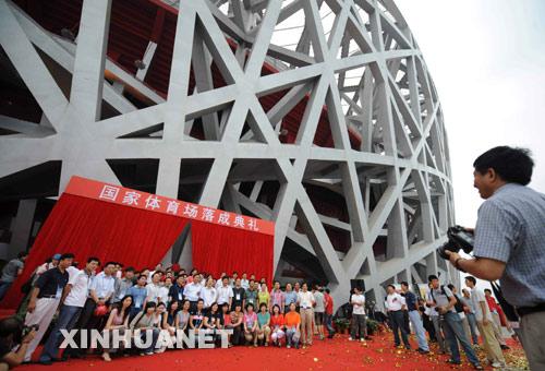 """6月28日,参加国家体育场建设的工作人员在""""鸟巢""""前合影留念。当日,国家体育场(鸟巢)举行落成典礼。 新华社记者罗晓光摄"""