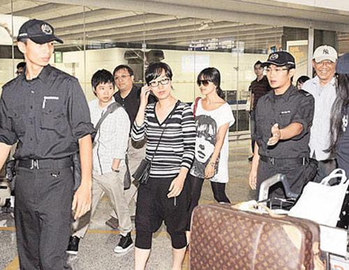 宋慧乔在工作人员护送下走出机场,面无表情
