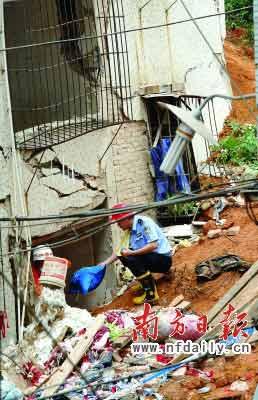 布吉一处山体滑坡致一名青年困在废墟。图为参加抢救的警察向被困者递氧气袋。本报记者朱丹阳摄