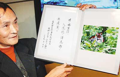 """2007年10月12日周正龙展示""""华南虎""""照片。新华社记者"""
