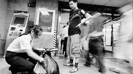 今早,在前门站,安检人员对乘客的大包进行手检 摄/记者杨威