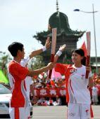 图文:奥运圣火在吴忠传递 火炬手击掌传递
