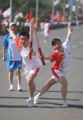 图文:奥运圣火在银川传递 刘倩女交接后庆祝