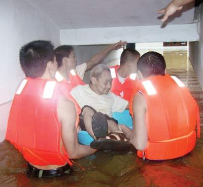 昨日,红安县社会福利院,消防人员站在齐腰深的积水中用塑料盆救出老人。通讯员