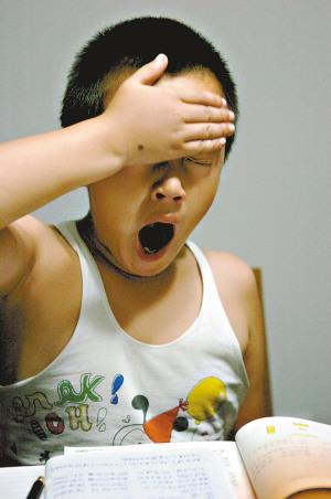 晚上10时,一位在做作业的小学生已经哈欠连天。