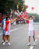 图文:奥运圣火在西安传递 吴丽花与施平交接