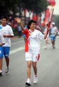 图文:奥运圣火在西安传递 火炬手吴丽花传递中