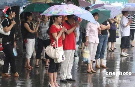7月4日上午,四川绵阳延期高考第二天,天空不作美下起了大雨,许多考生家长冒雨坚守在绵阳中学考点外,等待考生走出考场。中新社发吴芒子 摄