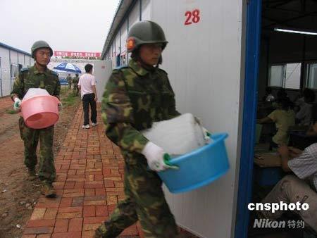 """7月3日,在四川省中江县三所中学的200间""""板房考场""""内,中国空降兵某部黄继光生前所在连百余名官兵在开考前30分钟将第一批""""降温冰块""""搬运到位,给当地5359名高考学生提供良好的考场环境。在为期3天的灾区高考时间内,他们将每天运送两次这样的""""降温冰块""""。中新社发刘烊宏 摄"""