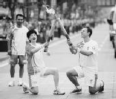 图文:奥运会火炬陕西西安传递 火炬手跪地交接