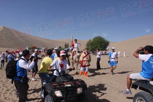记者争拍火炬手骑骆驼传圣火