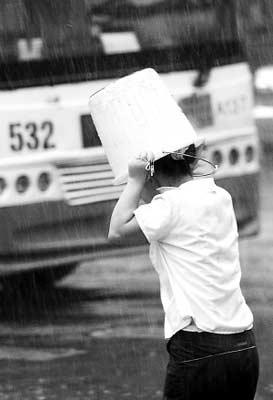 昨日傍晚时分,狂风大作,一场暴雨打得部分市民措手不及。图为17时53分,汉口天门墩,一位市民在暴雨中顶桶前行。记者苗剑 摄