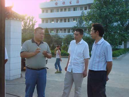 科力公司副总经理王海江(左二)正在向中江县教育局局长(右)介绍施工情况