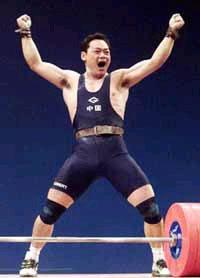 """1996年7月23日,70公斤级中国选手占旭刚将该项目金牌挂在了自己的脖子上,令人自豪的是,占旭刚还打破了70公斤级抓举、挺举和总成绩的三项世界纪录。显示了中国人""""力拔山兮气盖世""""的精神面貌"""