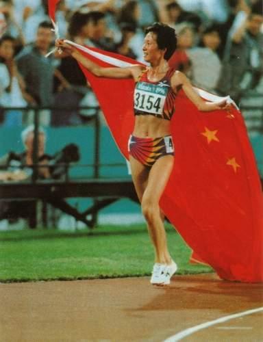 """1996年7月28日,中国选手王军霞在第26届奥运会女子5000米比赛中,以14分59秒88的成绩获得金牌。这位有""""东方神鹿""""美称的选手以如此绚丽的一笔,为自己的运动生涯画上了一个圆满的句号。当王军霞率先冲过终点后,看台上一位中国青年将手中的一面五星红旗交到她,王军霞把国旗披在身上,双手兴奋地舞动着旗角,环绕赛场,与看台上的每一位炎黄子孙共享胜利后的喜讯。和唐灵生那精彩的夺冠瞬间一样,王军霞这一""""经典画面""""至今仍深深地印在了国人的脑海中"""