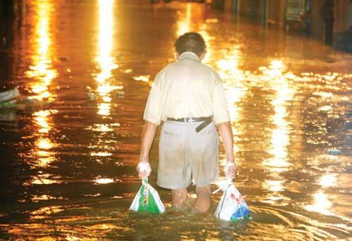 21时,长沙市岳麓区时代帝景酒店西侧小巷,一位老伯提着沙袋走在积水中。