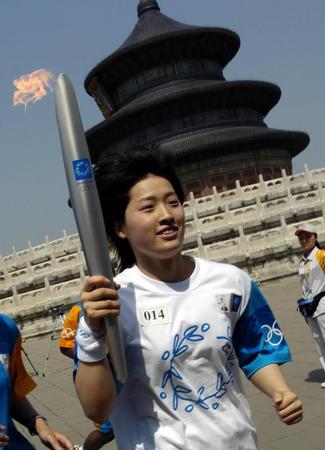 2004年6月9日,中国游泳运动员罗雪娟手举奥运火炬经过北京天坛祈年殿。