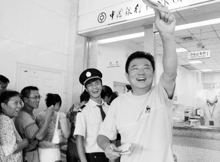 幸运地抢到首张纪念钞,他喜出望外  商报记者 张亮亮/摄