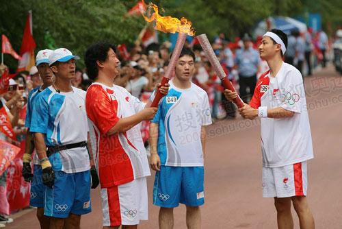 中国青年报摄影记者刘占坤在哈尔滨传递北京奥运火炬,图为刘占坤与上棒火炬手交接