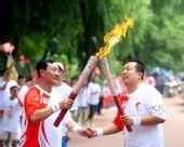 图文:奥运圣火在哈尔滨传递 火炬手手拉手交接