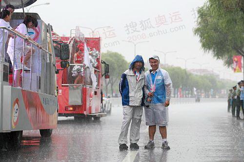 倾盆大雨中花车宝贝与路边群众为奥运加油,为中国加油