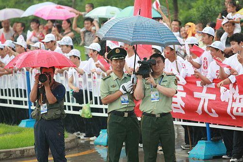 大庆群众向冒雨工作的火炬工作人员致敬