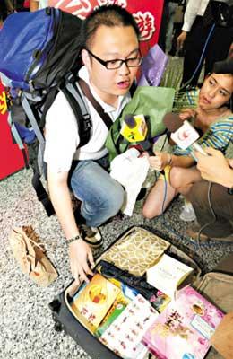 团友向记者展示自己买回的物品。 张伟清摄