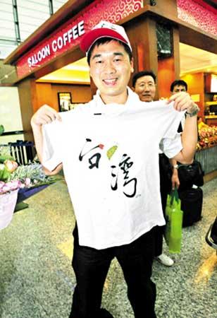 团友在机场展示在台湾买回的纪念衫。